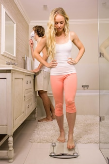 De blondevrouw gebruikt ongeveer een weegschaal terwijl haar vriend thuis scheert