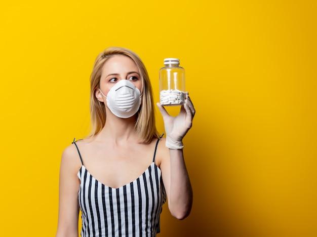 De blondevrouw in gezichtsmasker en handschoenen houdt kruik met pil