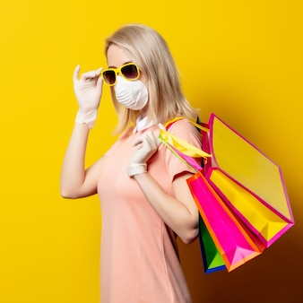 De blondevrouw in gezichtsmasker en roze kleding houden het winkelen zakken op gele muur