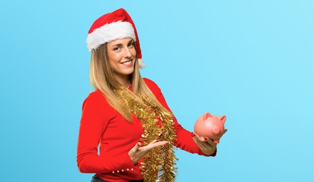 De blondevrouw kleedde zich omhoog voor kerstmisvakantie houdend een grote piggybank op blauwe achtergrond