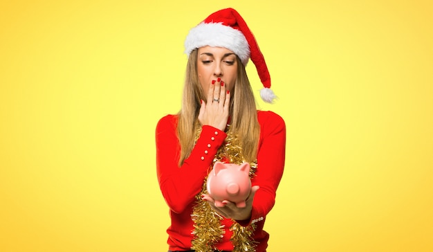 De blondevrouw kleedde zich omhoog voor kerstmisvakantie verraste terwijl het houden van een grote piggybank