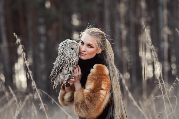 De blondevrouw met een uil in haar handen loopt in het bos in de herfst en de lente. lange haarvrouw, romantisch portret met uil. art fashion foto, mooie make-up