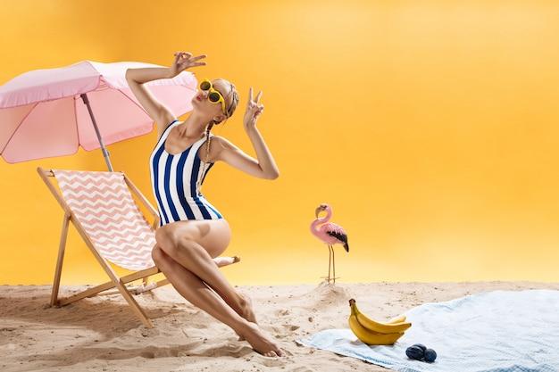 De blondevrouw op roze chaise-longue stelt met handen