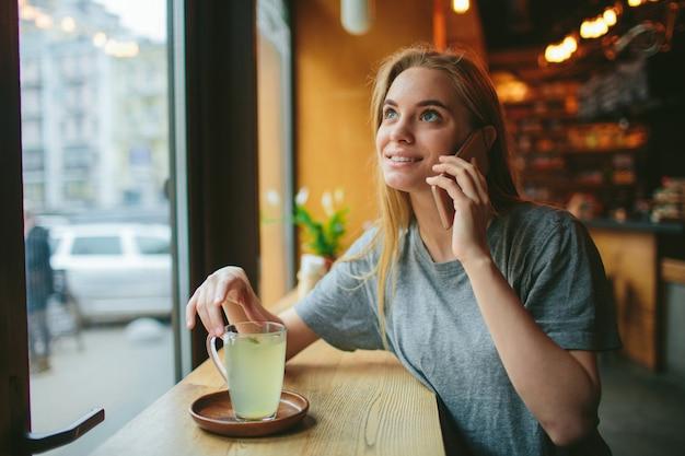 De blondine gebruikt de telefoon. meisje en smartphone. een vrouw zit in een café met een mobieltje.