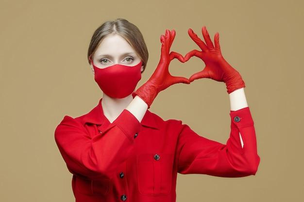 De blondine in rode handschoenen en een masker vouwde haar handen in de vorm van een hart. het concept van het voorkomen van coronavirus covid 19.