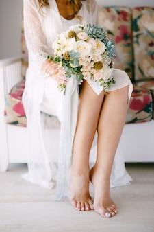 De blootsvoets bruid in een kanten gewaad zit op een bank in een hotelkamer en heeft een bruidsboeket in zich