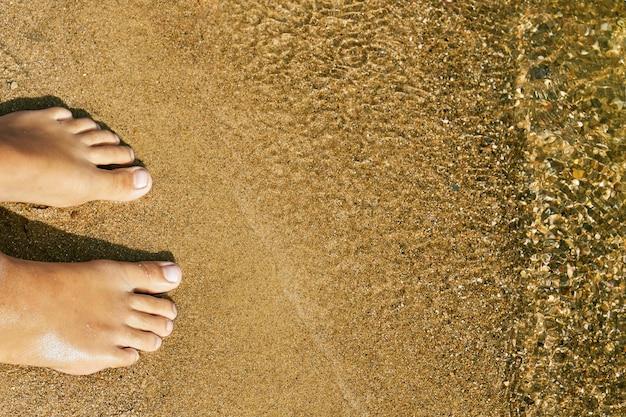 De blote voeten van het tienermeisje die zich op het zand van een meerstrand dichtbij het water op zomervakanties bevinden. concept van een rust op het strand in zomerse hitte