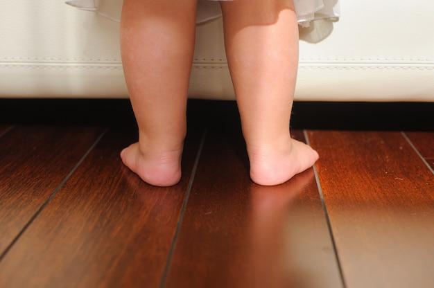 De blote voeten van kinderen, naast het bed