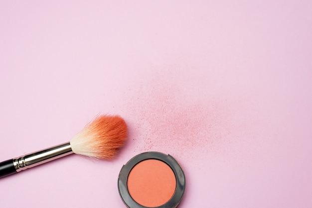 De blush brush ligt op een roze achtergrond naast de oranje geperste blush. poeder textuur op achtergrond
