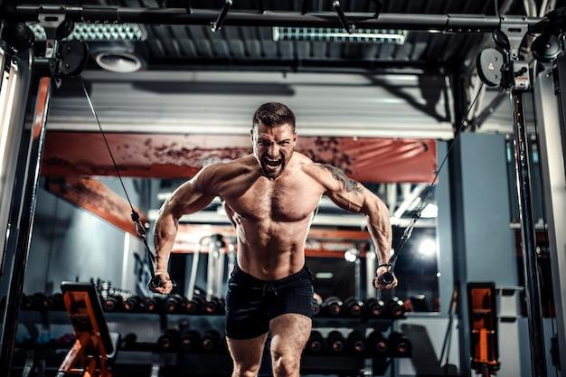 De bodybuilder werkt aan zijn borst met kabeloversteekplaats in gymnastiek