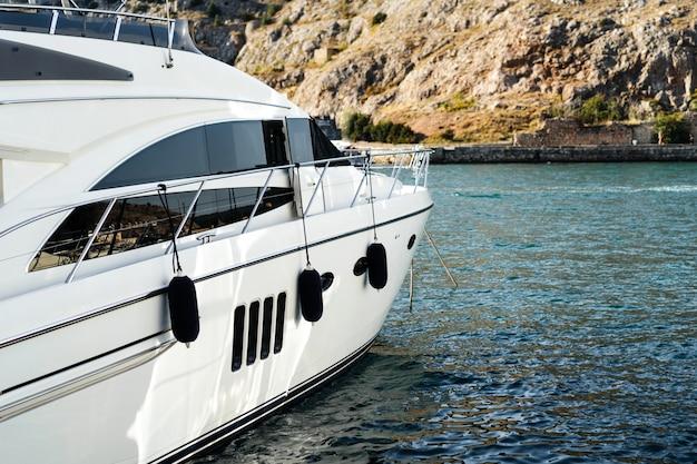 De boeg van een luxe wit jacht staat op de pier in een kleine havenbaai. bivakmuts krim.