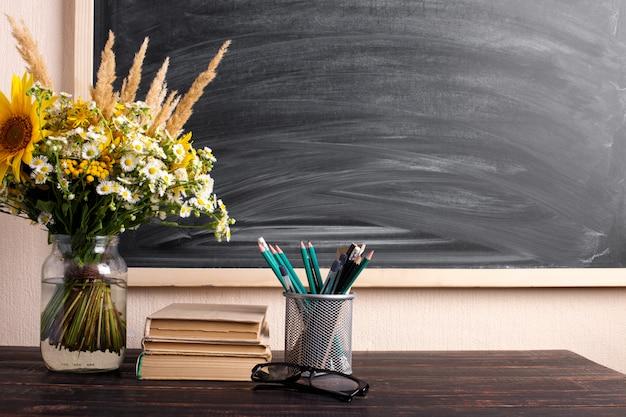 De boeken van de glazenleraar en het boeket van wilde bloemen op de lijst, bord met krijt. het concept van de dag van de leraar. kopieer ruimte.