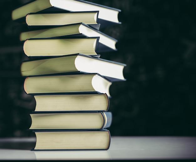 De boeken worden in een stapel boeken op tafel gelegd