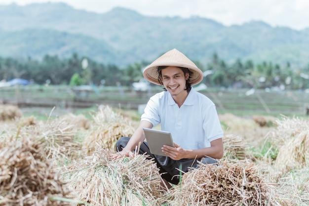 De boer glimlachte terwijl hij de opbrengst van de rijstoogst liet zien als hij een tablet in het veld gebruikte