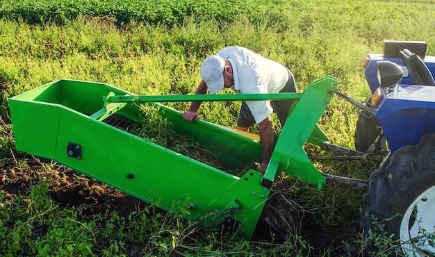 De boer inspecteert en repareert afstellingen van landbouwwerktuigen voor het rooien van aardappelen
