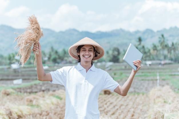 De boer met een hoed steekt zijn hand op als hij na de oogst rijstplanten en tablet draagt