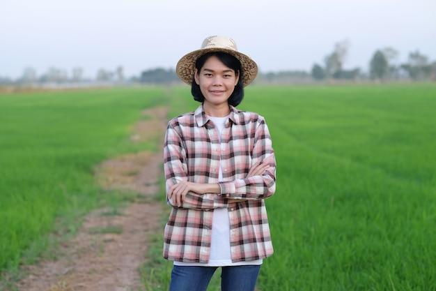 De boerin draagt een overhemd en een wit t-shirt staat op de groene rijstboerderij