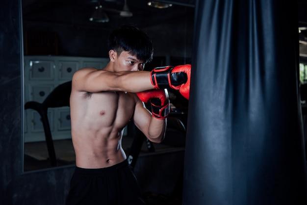 De bokser van de jonge mensen sterke sportenmens maakt oefeningen in gymnastiek, gezond concept