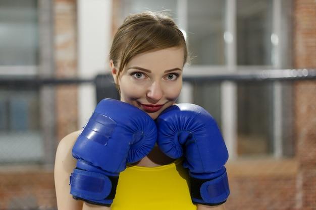 De bokservrouw met blauwe handschoenen sluit omhoog