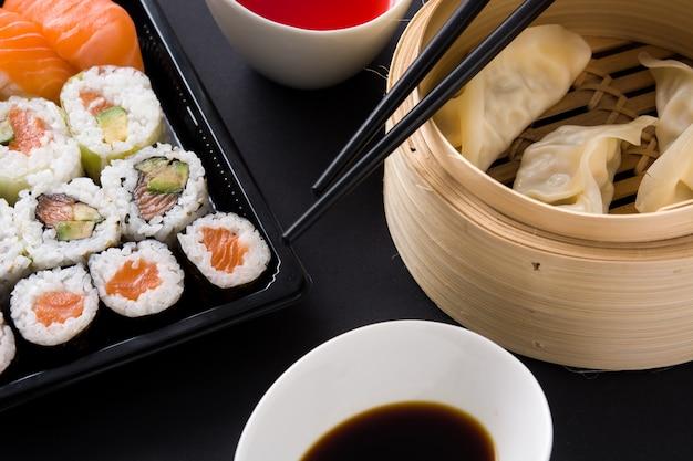 De bollen of gyoza dienden in traditionele stoomboot en sushi op zwarte dichte omhooggaand