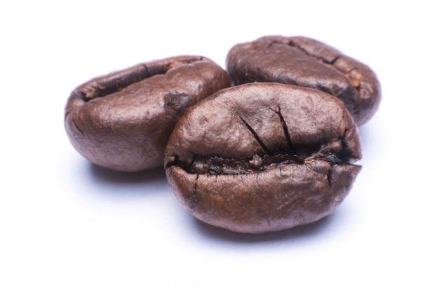 De bonen dichte omhooggaande die macro van de koffie op wit wordt geïsoleerd