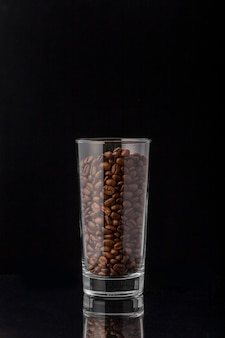De bonen van de vooraanzichtkoffie in lang glas