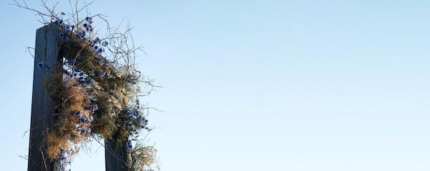 De boog is versierd met natuurlijke bloemen tegen de blauwe lucht in een prachtig park