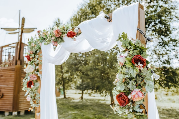 De boog versieren met bloemen en stof voor een huwelijksceremonie in de natuur