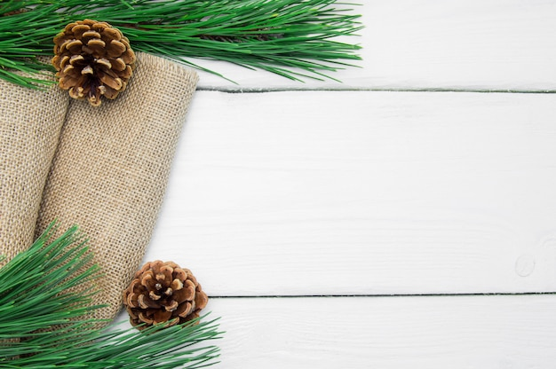 De boom en de kegel van takkerstmis op jute op witte houten uitstekende oppervlakte