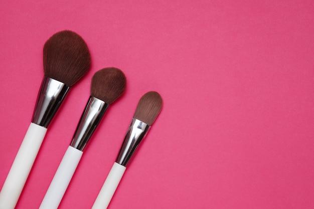 De borstels van de make-upkunstenaar op roze achtergrond