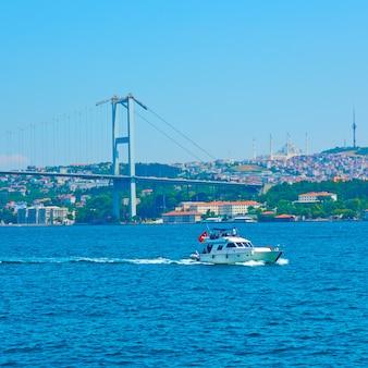 De bosporus-brug (15 juli martyrs bridge) en motorboot in istanbul, turkije