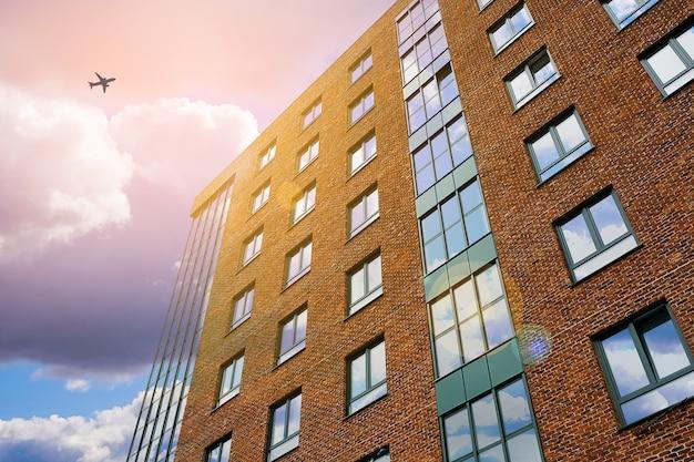 De bouw met meerdere verdiepingen van de baksteen tegen de hemel. in de wolken vliegend vliegtuig.