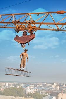 De bouw van de kraanholding met mannetje over stad.