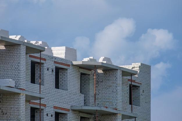 De bouw van een huis met meerdere verdiepingen van witte baksteen op een zomerdag op de achtergrond van wolken