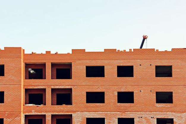 De bouw van nieuwe huizen met meerdere verdiepingen van rode baksteen.