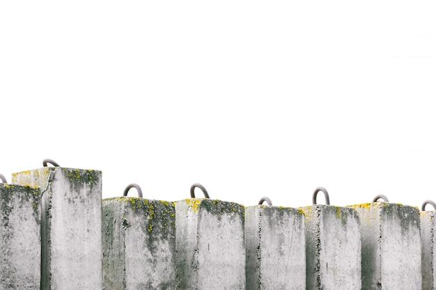 De bouw van vuile betonblokken met mos op een rij versterkt de rivieroever.