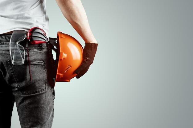 De bouwer, de architect houdt in zijn hand een bouwhelm