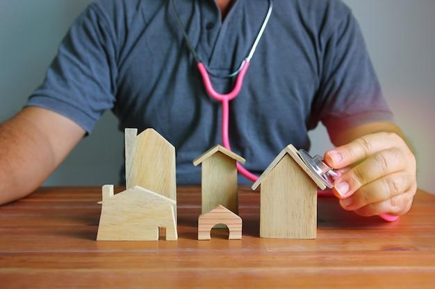 De bouwer die een stethoscoop gebruikt die het houten huis controleert