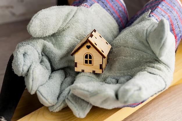 De bouwer houdt in werkhandschoenen model van het huis tegen de achtergrond van bouwmaterialen en hulpmiddelen.