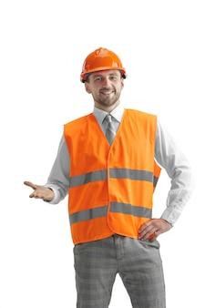 De bouwer in een bouwvest en een oranje helm die zich op witte muur bevindt. veiligheidsspecialist, ingenieur, industrie, architectuur, manager, beroep, zakenman, baanconcept