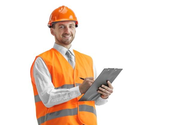 De bouwer in een bouwvest en een oranje helm die zich op witte studioachtergrond bevinden. veiligheidsspecialist, ingenieur, industrie, architectuur, manager, beroep, zakenman, baanconcept
