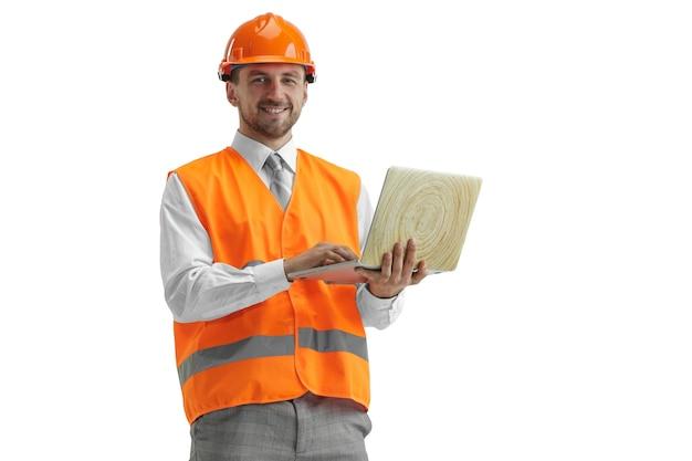 De bouwer in een bouwvest en een oranje helm met laptop. veiligheidsspecialist, ingenieur, industrie, architectuur, manager, beroep, zakenman, baanconcept