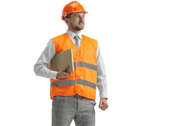De bouwer in een bouwvest en een oranje helm met laptop.