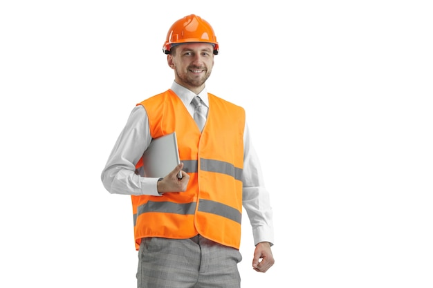 De bouwer in een bouwvest en een oranje helm met tablet.