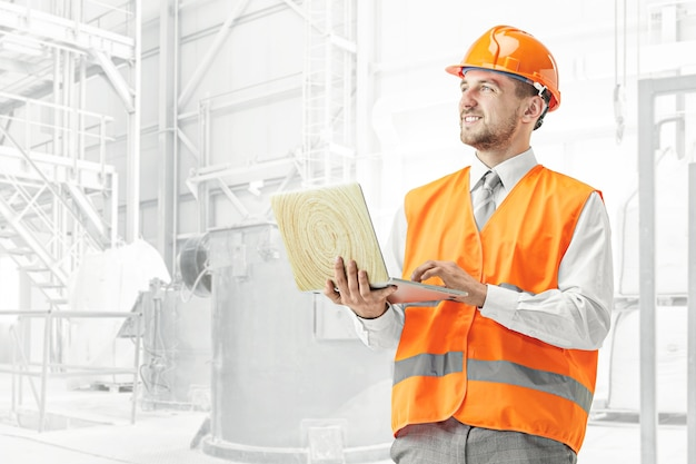 De bouwer in oranje helm tegen industrieel