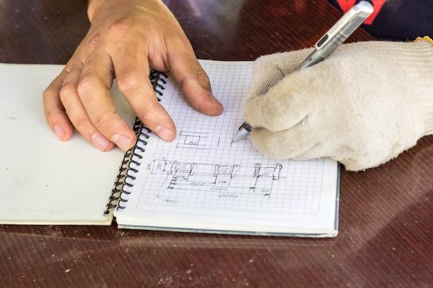 De bouwer maakt een schets van het huis. hand met een pen tekent