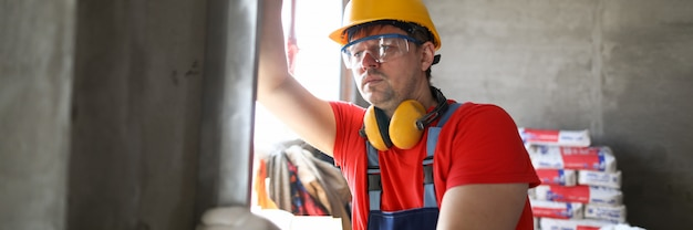 De bouwer meet niveaumuur bij bouwwerf