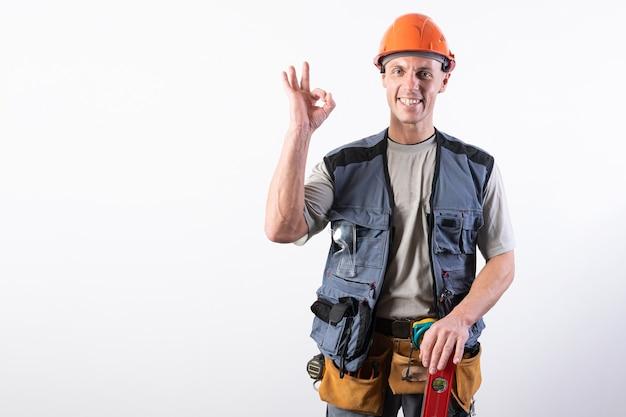 De bouwer toont het bord oke in werkkleding en helm op een lichtgrijze achtergrond