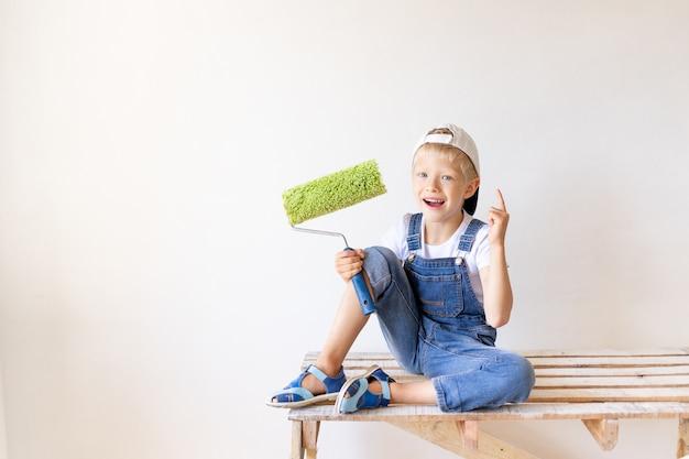 De bouwer van de kindjongen houdt bouwhulpmiddelen in een appartement met witte muren Premium Foto