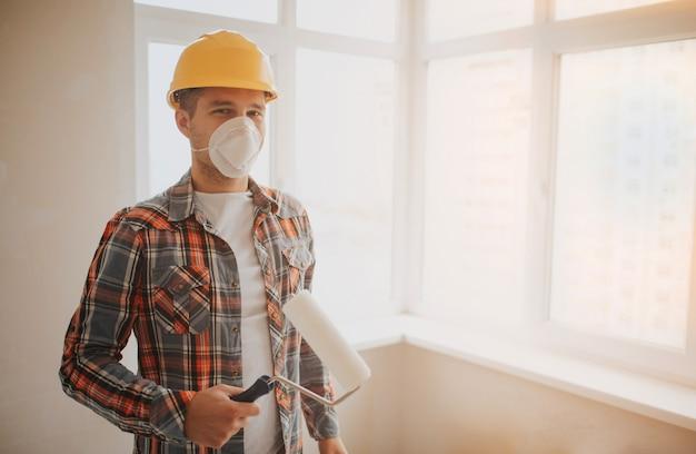 De bouwer werkt op de bouwplaats en meet het plafond. een arbeider in een oranje helm en een verfroller schildert de muur.
